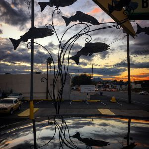 A sculpture of fish against a sunset and reflected in a car's roof outside Kingfisher, a restaurant in Tucson.