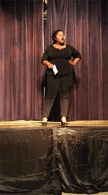 A student in black delivers her monologue