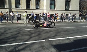 A hand cyclist flies toward the finish line