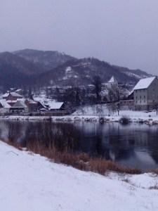 Dorf und Fluss im Schnee.