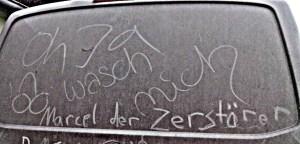 Mit Finger in Dreck gezeichnete Aufschrift auf Auto: Marcel der Zerstörer