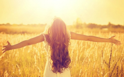 a-beautiful-girl-with-very-curl-long-hair-standing-on-the-wheat-field-in-sunshine-her-outstretched-arms-enjoys-the-freedom
