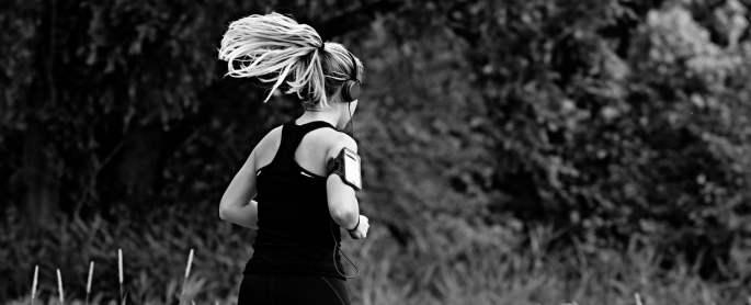 consigli running: donna che corre con i capelli al vento ascoltando musica