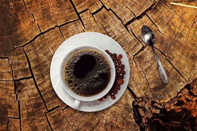 tazzina bianca di caffè su un piattino bianco con dei chicchi di caffè ed accanto un cucchiaino di argento. Posti su un tronco di albero tagliato.