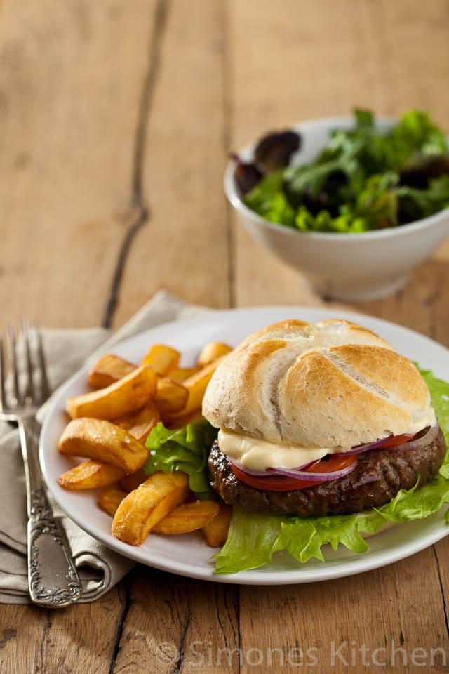 Hamburger with mayonaise, onionrings, salad and fries