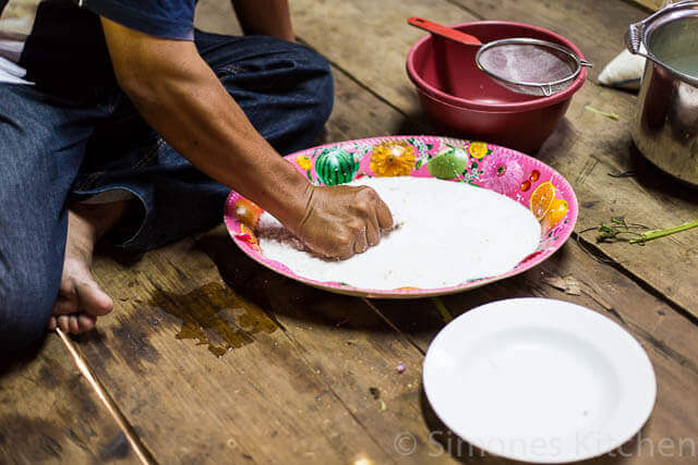 Kneden van de kokos om de kokosmelk te maken voor de curry