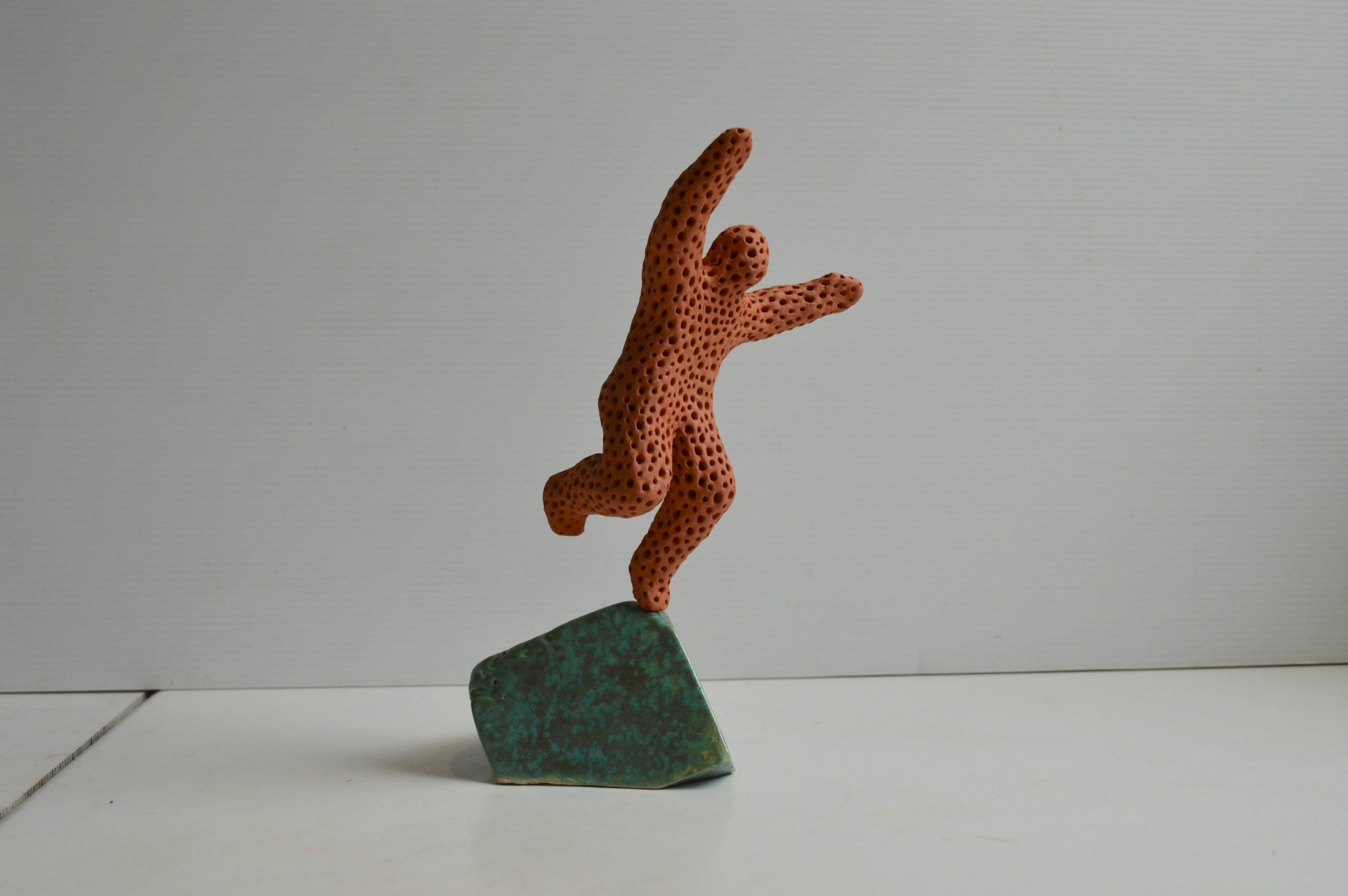 Leap of faith - patterned terracotta figure on a glazed base