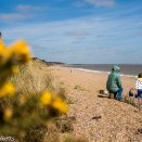 Dunwich Heath Suffolk pictures - A family playing on the beach in the background