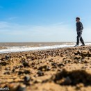 Dunwich Heath Suffolk pictures - A low perspective picture of a boy walking on the beach