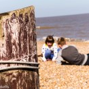 Dunwich Heath Suffolk pictures - A post in the foreground with a boy and girl playing in the background