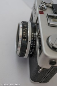 Minolta Hi-Matic F 35mm rangefinder camera showing focus scale and flash guide number