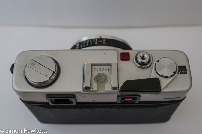 Minolta Hi-Matic F 35mm rangefinder camera showing shutter release, film advance and battery check