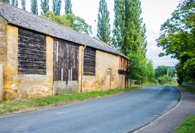 A cotswold stone barn by a road in Gloucestershire