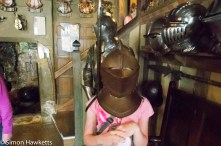 A girl trying on a suit of armour in Showshill Manor