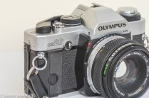 Olympus OM-20 35mm SLR - Side view showing rewind switch and bolt on grip