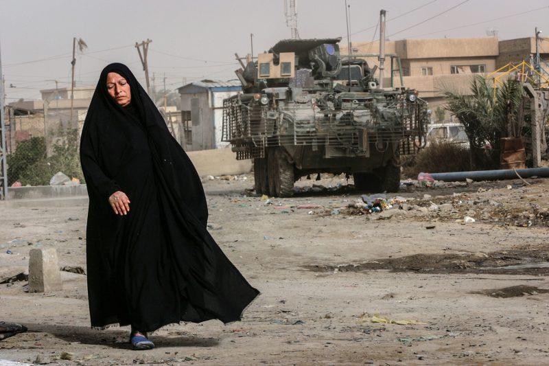 Eine Irakerin passiert im südlichen Teil Bagdads einen Stryker Radschützenpanzer der US-Armee. (c) Simon Klingert