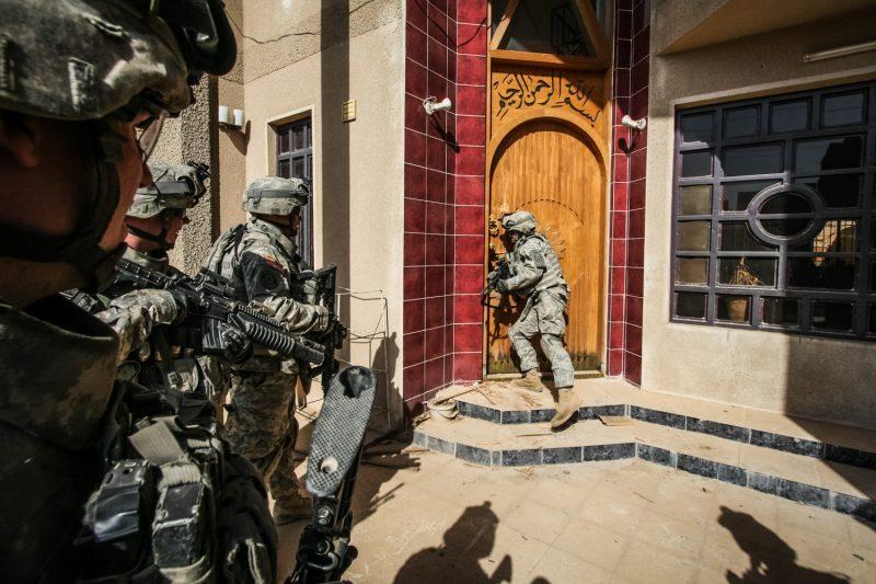 Bei der Suche nach Waffen und Sprengstoff brechen US-Soldaten die Tür eines verlassenen Hauses in Bagdad auf. (c) Simon Klingert