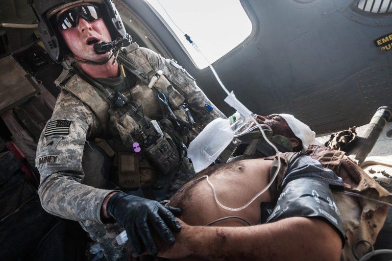 Der Flight Medic kümmert sich um einen schwer verwundeten afghanischen Polizisten, dessen Fahrzeug auf eine Sprengfalle gefahren war. (c) Simon Klingert