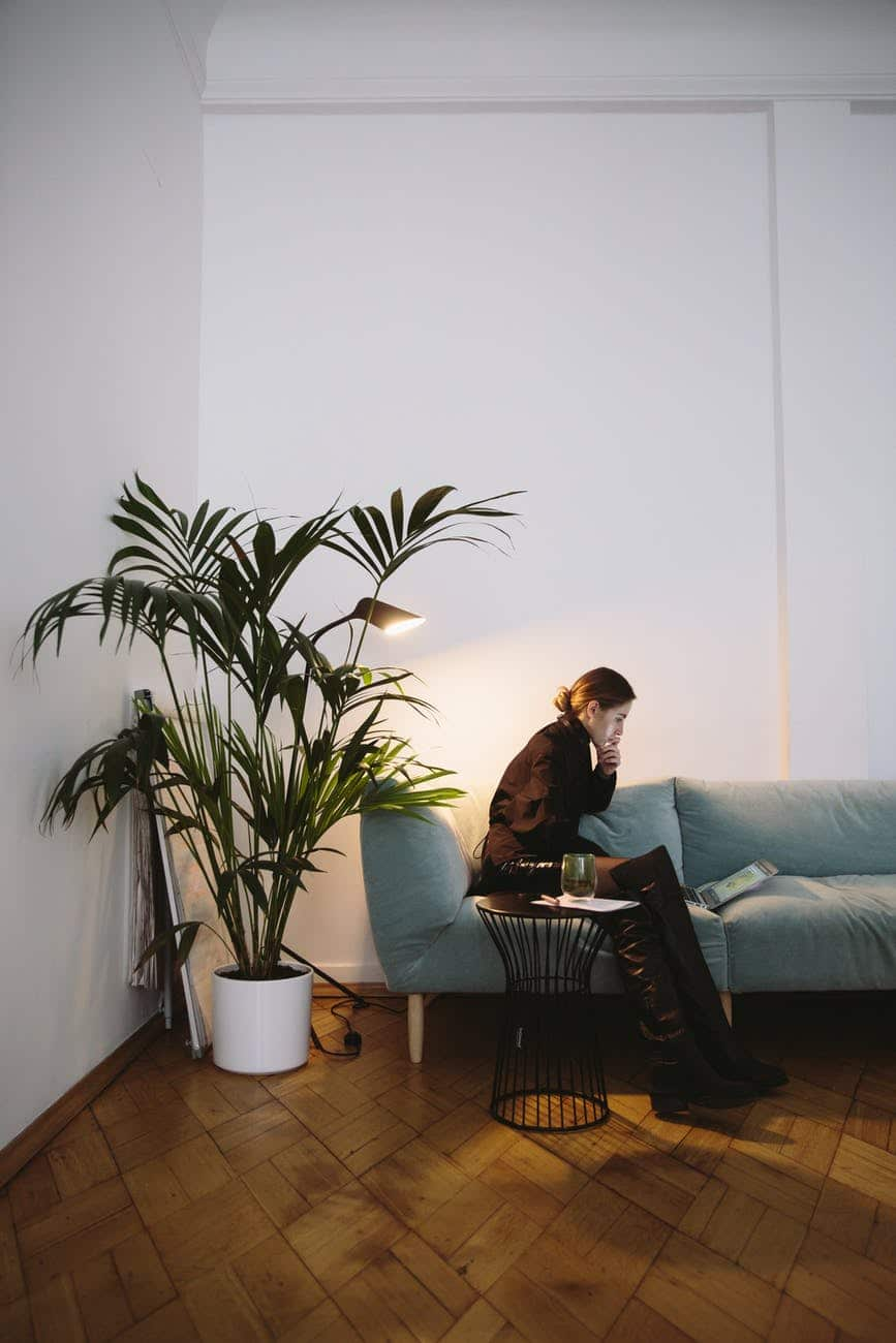 photo of woman sitting beside indoor plant