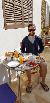 Simon with Breakfast with house background