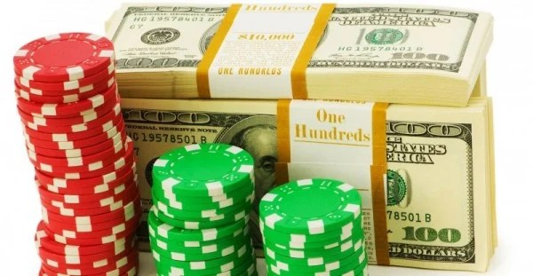 The picture depicts red and green casino bonus chips stacked. The casino bonus chips are in front of a stack of dollar bills.
