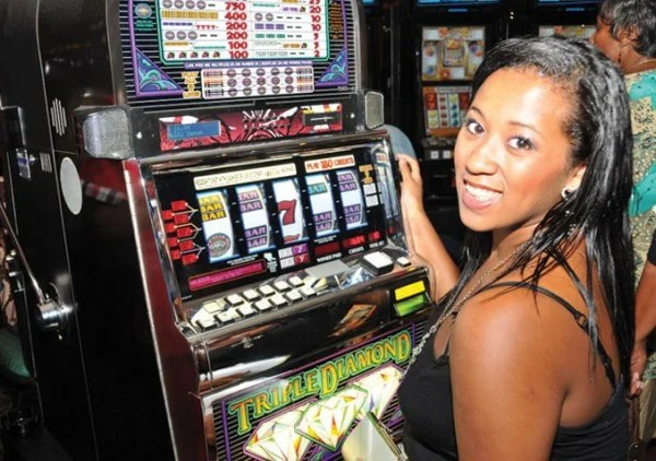 This is a picture of a native local creole woman playing the Triple Diamond slot machin in the Ma Pau Entertainment Centre, a casino-like slot parlour located in the Commonwealth of Dominica. On this page you can read about the legal status of online bingo, online poker, online sports betting, online lottery, online casino games of chance, cryptocurrency wagering, and a list of licensed online gambling sites accepting players from Dominica.