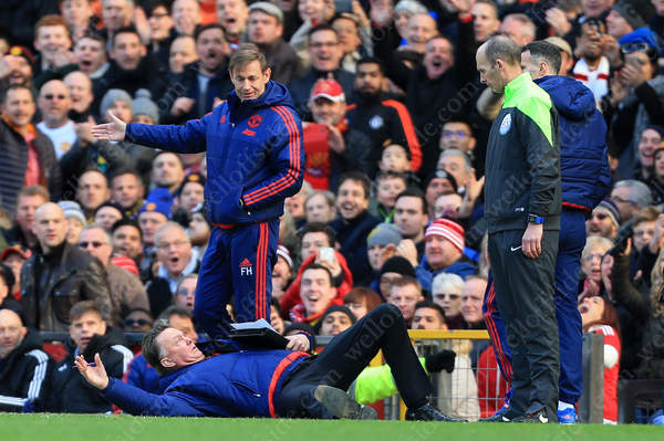 GONE: Man Utd manager Louis van Gaal imitates a dive in front of fourth official Mike Dean