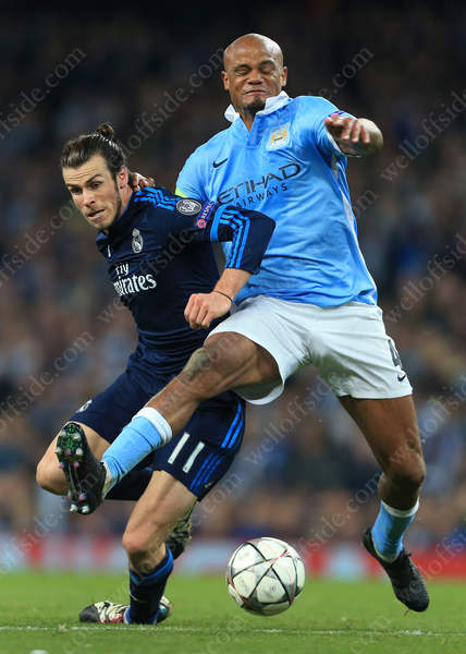 Gareth Bale of Madrid tussles with Vincent Kompany of Man City