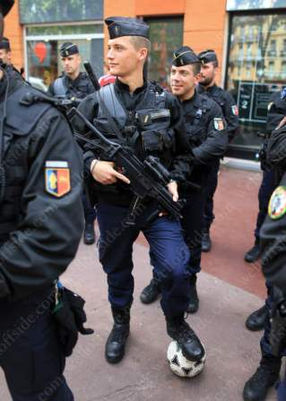 A Gendarmerie officer keeps control of a football