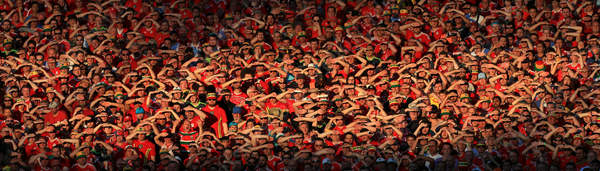 Welsh fans shield their eyes from the low evening sunlight