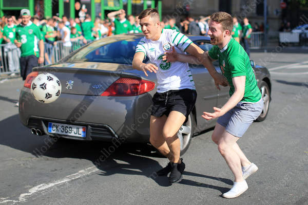 Irish fans compete to get hold of the ball as traffic passes by shortly before the road is closed