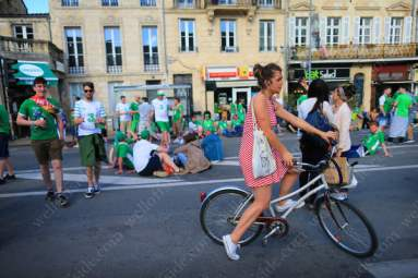 A local woman on a bike decides to turn around after cycling into a sea of green and white shirts