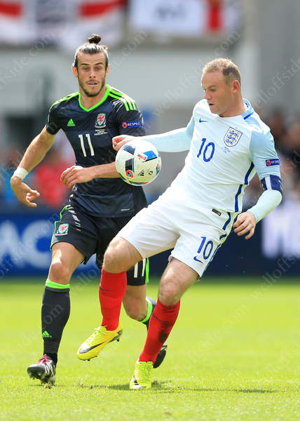 Wayne Rooney (R) and Gareth Bale compete for the ball