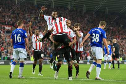 Lamine Kone of Sunderland is carried by teammate Younes Kaboul of Sunderland as he celebrates after scoring their 3rd goal against Everton