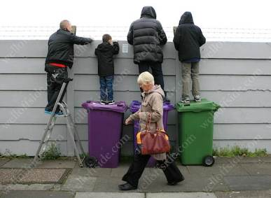 Liverpool fans stand on wheelie bins to watch their team train at Melwood