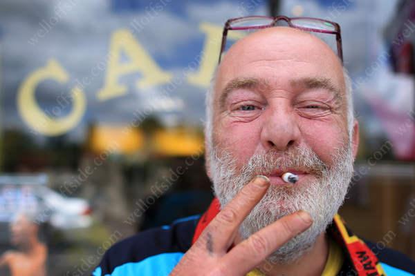 A Watford fan enjoys a cigarette outside a cafe