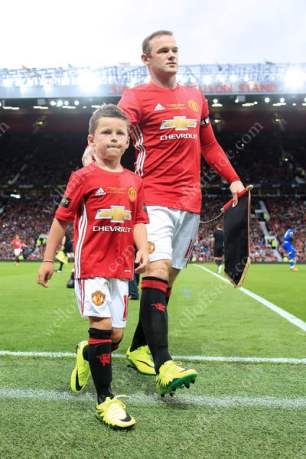 Wayne Rooney ushers his son, Kai, from the pitch ahead of his testimonial match against Everton