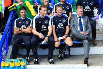 New Everton manager Ronald Koeman (R) takes his place on the bench