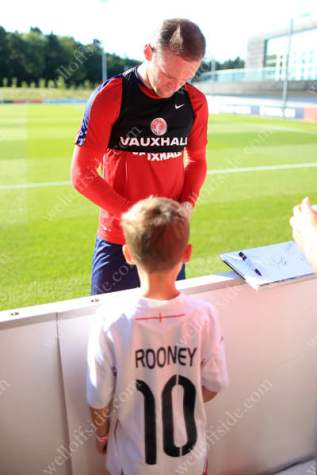 A young Wayne Rooney fan gets an autograph from his hero