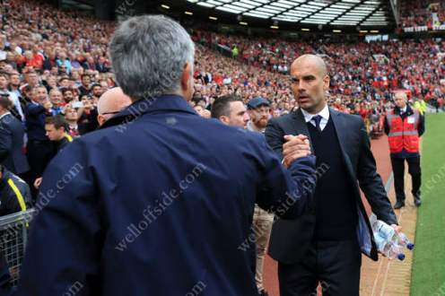 New Man City manager Pep Guardiola (R) greets Man Utd's new boss Jose Mourinho ahead of their first Manchester Derby