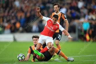 Harry Maguire of Hull tackles Alexis Sanchez of Arsenal