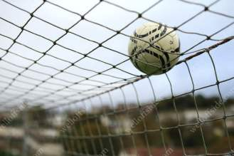 A football rests on top of the goal net
