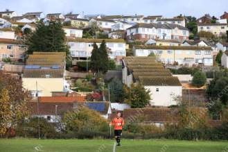 Rows of houses overlook the Coombe Valley pitch as Teignmouth's goalkeeper stands by