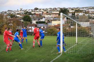 Rows of houses overlook the pitch as players compete for the ball in the goalmouth