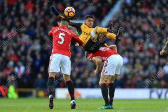 Alexis Sanchez of Arsenal goes over Michael Carrick of Man Utd (R) and Marcos Rojo of Man Utd