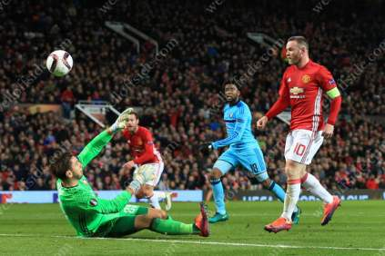 Wayne Rooney of Man Utd chips the ball over Feyenoord goalkeeper Brad Jones and scores their 1st goal of the game to become the club's all-time leading goalscorer in European competition