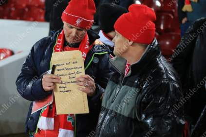 A Liverpool fan holds an envelope with a list of autographs required written on it before his side's match against Chelsea