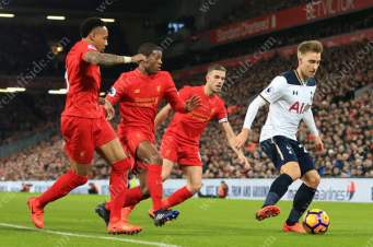 Christian Eriksen of Spurs battles with Liverpool players Nathaniel Clyne (L), Georginio Wijnaldum (C) and Jordan Henderson