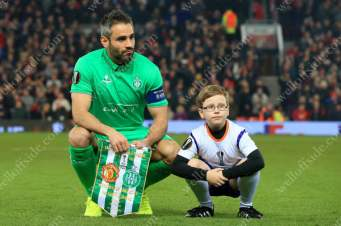 Loic Perrin of St. Etienne crouches down with the mascot before their team group photo prior to the UEFA Europa League match against Manchester United