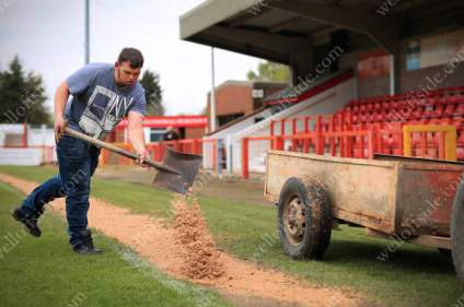 A groundsman spreads sand over the linesman's path along the touchline ahead of Northwich Victoria's match against Witton Albion